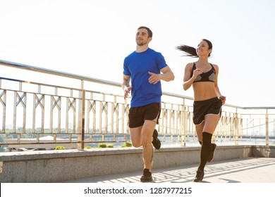 Two sporty friends wearing tracksuits running in morning on waterfront. Muscular man and slim fit woman training together, laughing and enjoying time. Healthy lifestyle and sport concept.