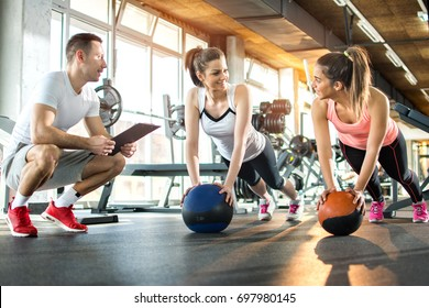 Two sporty girls exercising with fitness balls while their fitness instructor tracking the progress on clipboard.