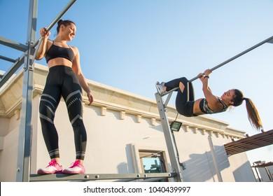 Two sporty girls having fun during calisthenics training outdoors.