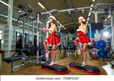 Two sporty girls in Santa Claus costumes at the gym in Christmas and New Years.
