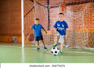 Two sporty young boys on an indoor court playing in the goalposts, one bouncing a basketball and the other standing on a soccer ball