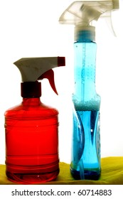 Two sprayers, one red and one blue, over yellow flannel