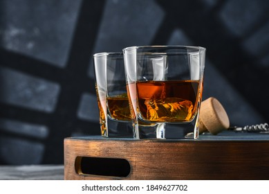 Two square glasses of whiskey with ice on a wooden tray, on a blue background. Two square glasses of brandy on a wooden tray, on a blue background.