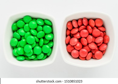 Two squared bowls with small green and red coated chocolate candies similar to m&ms in a squared bowl isolated on white background, top view