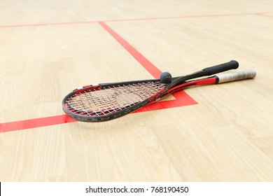 two squash rackets and ball on the wooden floor. Racquetball equipment on the court on red lines. Photo with selective focus