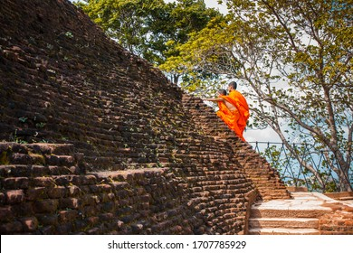 Two Sri Lankan Buddhist monks climb the stairs to Mount Sigiriya, Sri Lanka. Orange monks clothes develop in the wind