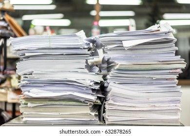 Two stack of paper lay on a messy office table.