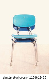 Two stacked blue school chairs