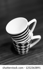Two stacked espresso cups with line and square patterns in black and white and soft focus.