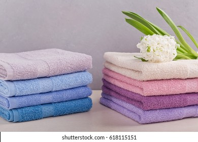 Two stacks of colorful bath towels with hyacinth flower on light background. Pastel colors cotton towels. Hygiene, fabric,spa and textile concept