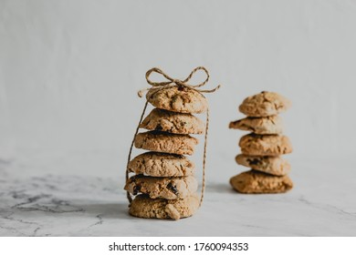 Two stacks of oatmeal cranberry cookies tied up with a packthread