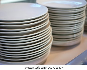 Two stacks of plain white dinner plates on a plain wooden table