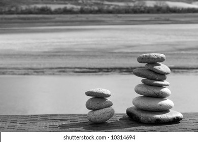 Two stacks of rounded river stones rest on weathered wood in front of a soothing natural background.