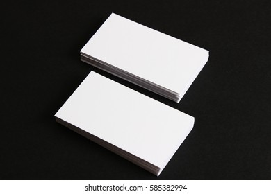 Two stacks of white business cards on a black background .