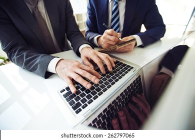 Two staff members working with laptop and notebook.