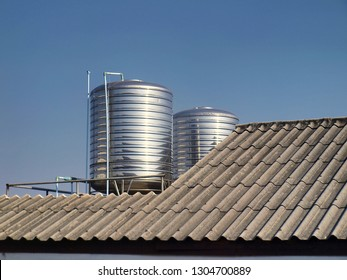 Two stainless steel water tanks on the roof For water storage, used in homes and water reserves, used when water is not available On the background is the roof of the house and the blue sky.