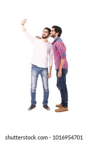 Two standing friends taking a selfie, one of them puts his hand on his friend's shoulder, isolated on a white background.