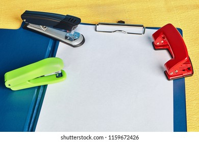 Two staplers and hole puncher lie over office folder with a spring clip or clipboard  and the blank of white  paper, with copy space, mockup for design.