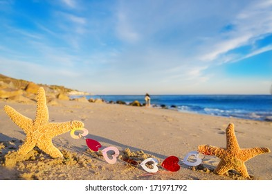 Two Starfishes with hearts on the sandy beach by the ocean