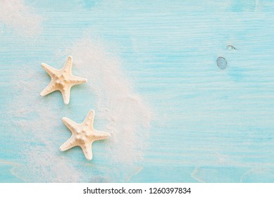 Two starfishes and white sea sand are on the background of blue faded wooden deck. Marine concept