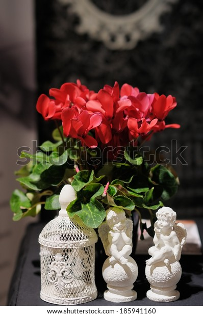 Two statuettes of angels and red flowers  as a decoration on table
