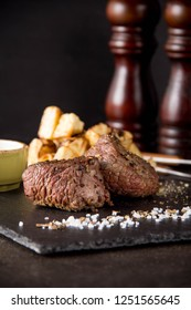 Two steak filet Mignon with a side dish of baked potatoes and celery, with salt and pepper. Beautiful restaurant serving