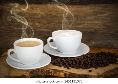 Two steaming cups of hot coffee  on old wooden background with roasted coffee beans as symbol for cozy breakfast