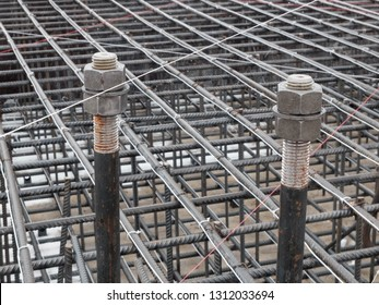 Two steel anchor bolts with screw nuts and steel grid on tower crane footing reinforcement