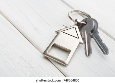 Two steel keys with house shaped trinklet on keyring on white wooden background with copy space. Home key, safety, security, real estate and rent concept