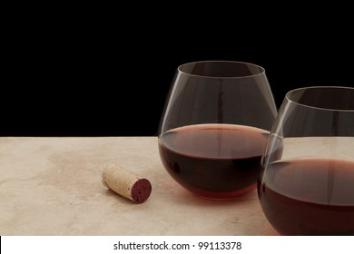 two stemless glasses of red wine served on a bar top isolated on black