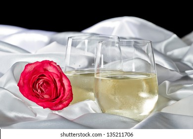 two stemless glasses of white wine served on a white silk