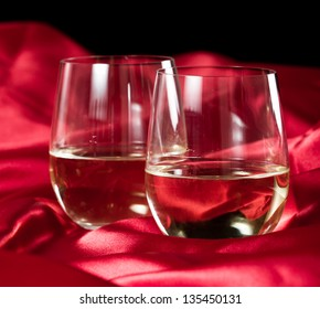 two stemless white wine glasses served on a red silk table cloth