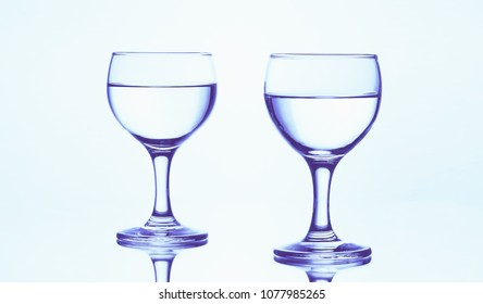 Two stemmed glasses of water isolated on a white background with mirror reflection.