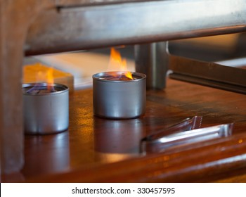 Two sternos with flames under a warming buffet tray