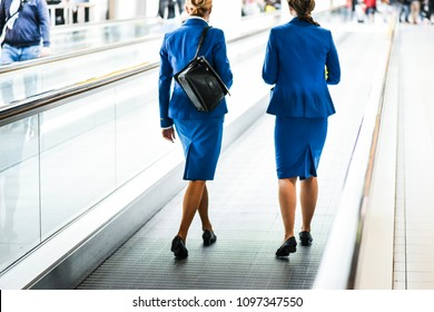 Two stewardess walking through escalator in back light on airport.