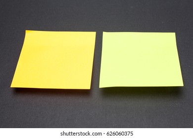 two sticky note on black background