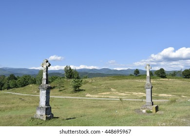 two stone crosses at a hill top.