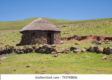 Two stone rondavels with traditional thatched roofs.  Traditional Basotho homes are round or rectangular-shaped structures made of stone and dung with roofs made of thatch (grass).