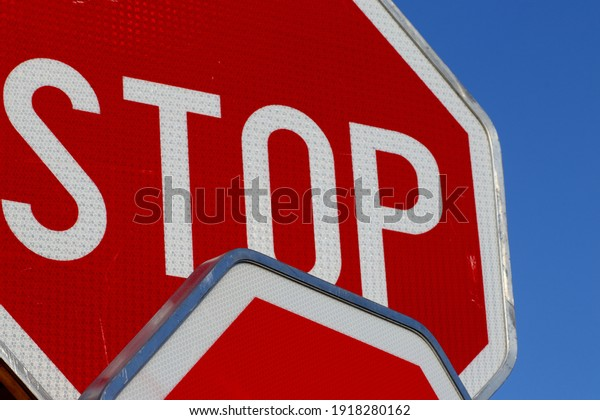Two stop signs on blue sky