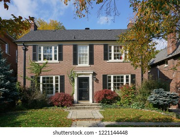 Two storey brick house on a sunny fall day