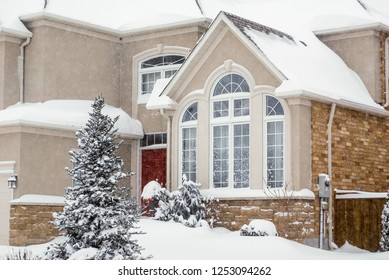 Two storey brick house with small trees in winter