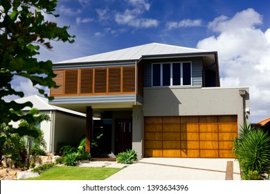 Two storey modern home with wooden garage and blue sky