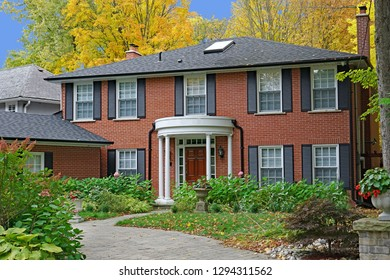 two story brick house surrounded by trees with fall colors