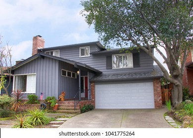 Two story ranch style house, gray wood siding with red brick work. Ranch style  is a domestic architectural style originating in the United States.