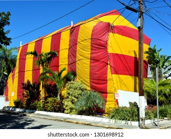 A two story residence is covered by a red and yellow tent for the poisonous chemical extermination of termites.