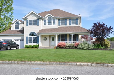 Two Story Suburban Home Landscaped with Pink Azaleas Japanese Maple Front Lawn Grass Curb