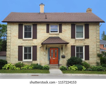 two story yellow brick house with shutters