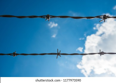 Two strands of barbed wire with blue sky and clouds in the background