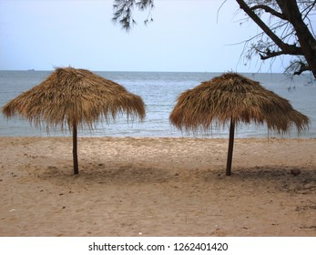 Two straw umbrellas on beach