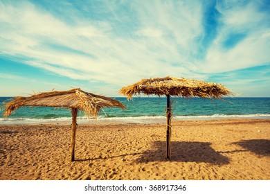 Two straw umbrellas on sandy beach